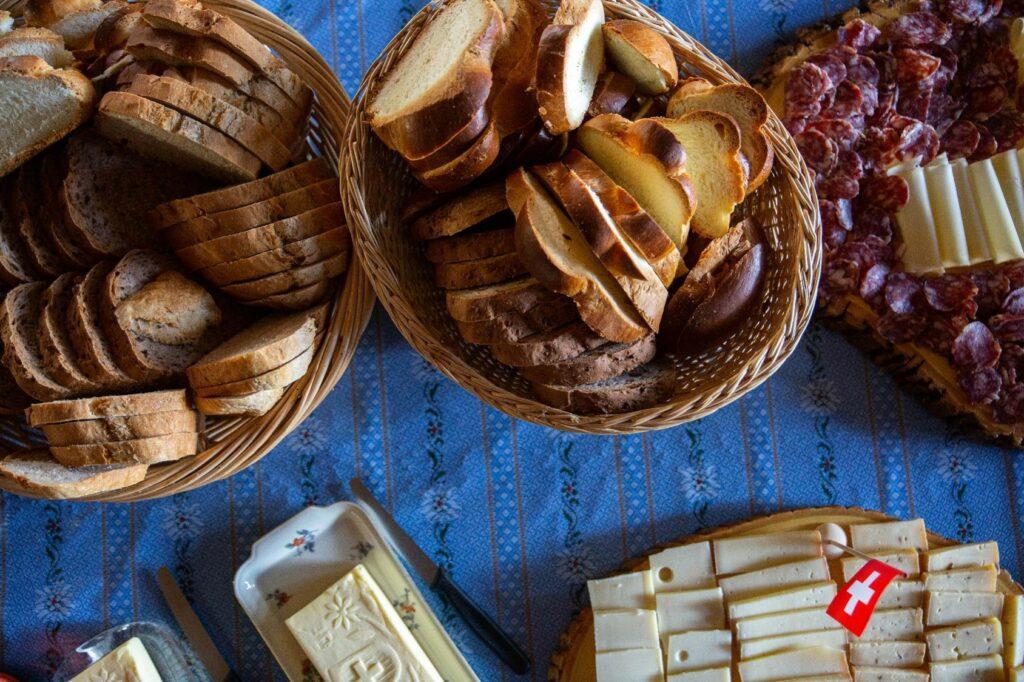 Ein Brunch-Buffet-Tisch mit Brot, Zopf, Fleisch, Käse und Butter.