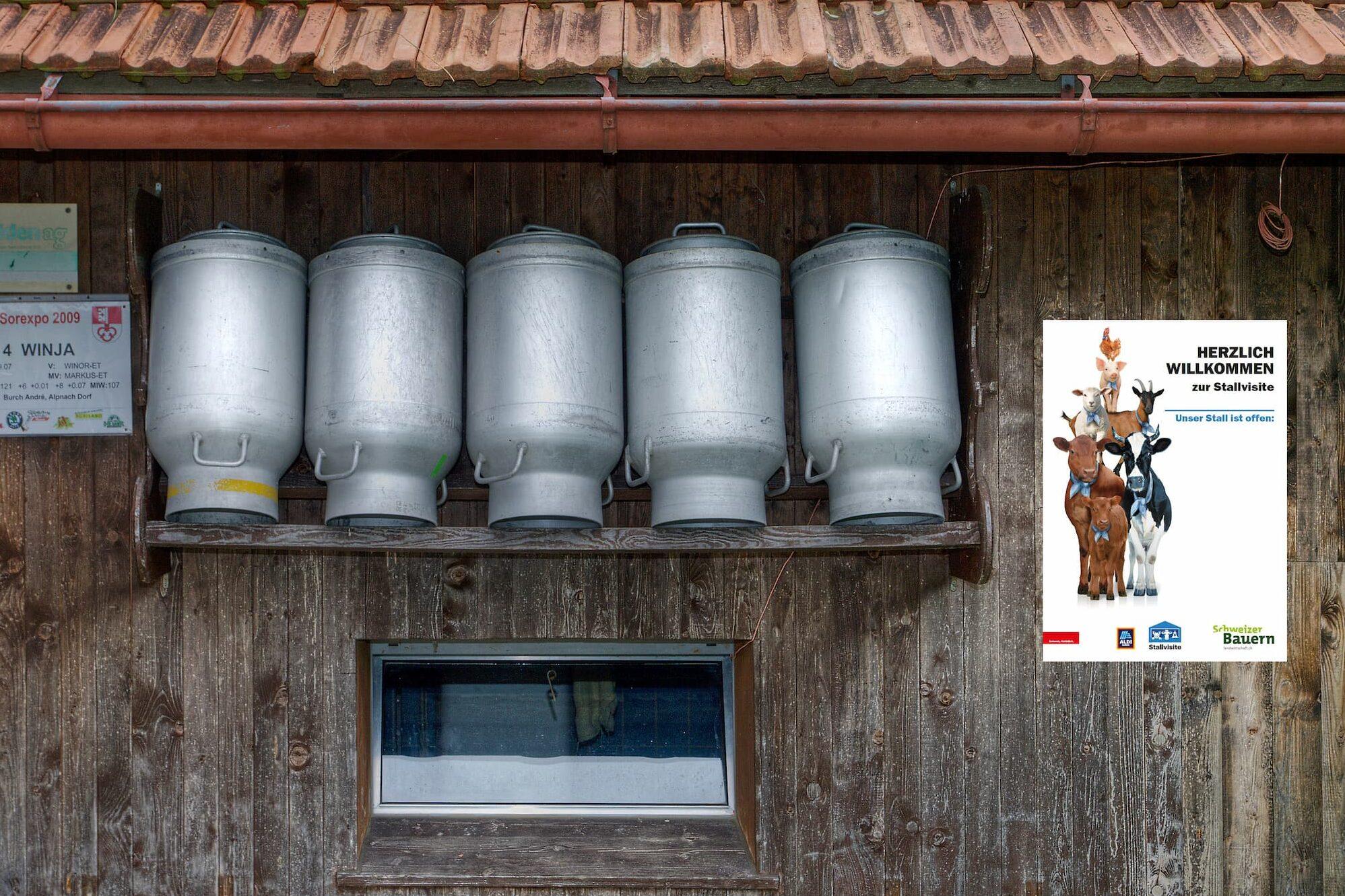 Milchkannen und eine Tafel zur Stallvisite an der Scheunenwand.