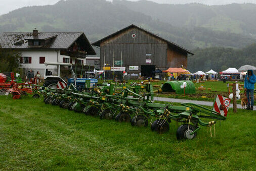Ein Traktor und verschiedene Anhänger auf einer Wiese aufgelistet.